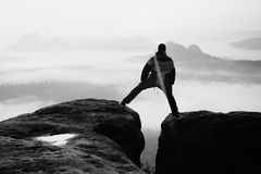 Hiker in black is jumping between the rocky peaks. Wonderful daybreak in rocky mountains, heavy orange mist in deep valley. Miracl Royalty Free Stock Photo