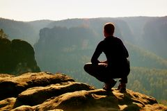 Hiker in black on  peak. Wonderful daybreak in mountains, heavy orange mist in deep valley. Man sit on the rock. Stock Images