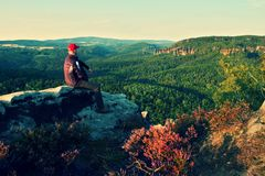 Hiker in black with red baseball cap on sharp  cliff and watch to valley. Colorful summer day. Stock Image
