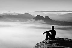 Hiker in black on the rocky peak. Wonderful daybreak in mountains, heavy orange mist in valley. Man sit on the rock. Stock Photography