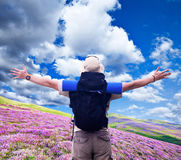 Hiker with black rucksack spreads hands expressing happiness Royalty Free Stock Photos