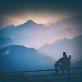 Hiker and blue morning fog. Instagram stylisation. Man sitting on a wooden fence and enjoy mountain valley covered with blue morning fog. Instagram stylisation Stock Images