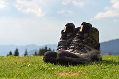 Hiker boots at the grass. In mountains Royalty Free Stock Photo