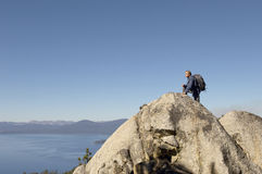 Hiker On Boulder At Coast. Side view of male hiker on boulder at coast Stock Images