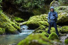 Hiker boy by the river. Young boy hiker with backpack near a river with mossy boulders Stock Photography