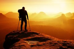 Hiker with broken leg in immobilizer. Deep misty valley bellow silhouette. Tourist with medicine crutch above head achieved mountain peak. Hiker with broken leg Royalty Free Stock Images