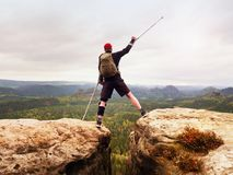 Hiker with broken leg in immobilizer. Tourist with medicine crutch above head achieved peak. Hiker with broken leg in immobilizer. Tourist with medicine crutch Royalty Free Stock Photography