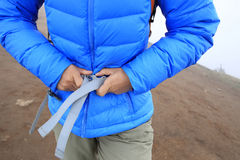 Hiker buckle up the belt of backpack on mountain peak Stock Images