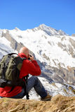 Hiker with camera and backpack taking picture of beautiful mount. Man hiker with camera and backpack taking picture of beautiful mountain Royalty Free Stock Photos