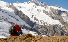 Hiker with camera and backpack taking picture of beautiful mount. Man hiker with camera and backpack taking picture of beautiful mountain Stock Images