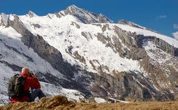 Hiker with camera and backpack taking picture of beautiful mount. Man hiker with camera and backpack taking picture of beautiful mountain Royalty Free Stock Photography