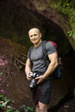 Hiker with camera near a cave Royalty Free Stock Photos