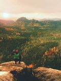 Hiker with camera on tripod takes picture from rocky summit. Alone photographer at edge photograph landscape Stock Photo