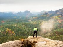 Hiker with camera on tripod takes picture from rocky summit. Alone photographer at edge photograph landscape Royalty Free Stock Photography