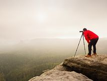 Hiker with camera on tripod takes picture from rocky summit. Alone photographer  on summit. Hiker with camera on tripod takes picture from rocky summit. Alone Stock Photo