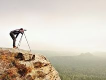 Hiker with camera on tripod takes picture from rocky summit. Alone photographer  on summit Royalty Free Stock Photo