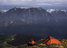Hiker camping across valley and massive cliff mountains. A hiker rests and enjoys the view after a long road through mountains trails Stock Image