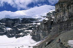 Hiker in Canadian Rockies. A hiker walks across rocks and steep cliffs at Plain of the Six Glaciers in Banff National Park in Alberta, Canada Royalty Free Stock Photography