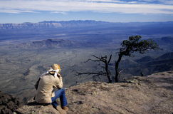 Hiker at Canyon Overlook. A hiker pausing to enjoy the spectacular view from an overlook at the edge of the canyon on South Rim Trail in the Big Bend National Royalty Free Stock Photo