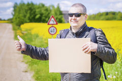Hiker with cardboard try to stop car on rural road Stock Images