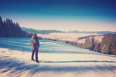 Hiker in a Carpathian winter mountain valley. Vintage Royalty Free Stock Image