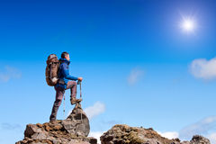 Hiker celebrates on the summit. With sunlight and copy space Stock Photo