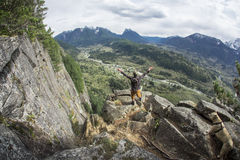 Hiker on Cliff High Above Small Town in Valley with Mountain Range in Distance Stock Photos