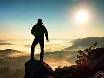Hiker climbed on peak of rock above valley. Man watch over misty and foggy morning valley Stock Images