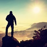 Hiker climbed on peak of rock above valley. Man watch over misty and foggy morning valley Royalty Free Stock Image