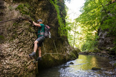 Hiker climbing above the river Stock Photography