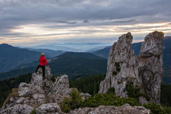 Hiker climbing high mountain rocks Stock Photos
