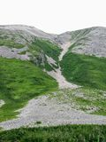A hiker climbing a massive scree slope on the way to the summit. Of Gros Morne Mountain, in Gros Morne National Park, Newfoundland and Labrador, Canada Stock Photos