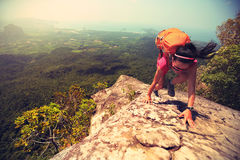 Hiker climbing rock on mountain peak cliff. Young asian woman hiker climbing rock on mountain peak cliff Royalty Free Stock Image