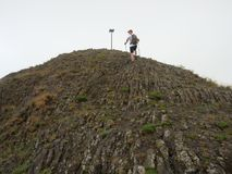 Hiker climbing on sharp peak of basalt formation of volcano Royalty Free Stock Image