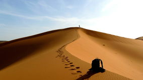 Hiker climbing to the top of the Great Sand Dune in the red dune sea of Erg Chebbi, Morocco. Royalty Free Stock Photography