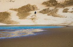 Hiker climbing up a sand dune Stock Photo