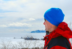 Hiker on the coast of the bay, covered with ice Royalty Free Stock Photo