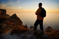 Hiker on coastline at sunset Stock Image