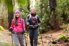 Hiker couple backpackers hiking in forest. On path in mountains Royalty Free Stock Images