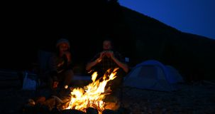 Hiker couple eating food near campfire 4k stock video footage