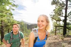 Hiker couple hiking in forest. Romantic hikers enjoying hike in beautiful mountain forest landscape. Blonde women hiker and Caucasian men on Gran Canaria Stock Photo