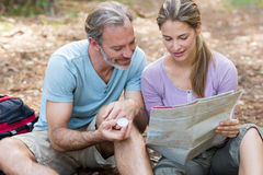 Hiker couple holding compass and reading map Royalty Free Stock Photo