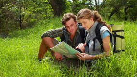 Hiker couple with map pointing ahead stock footage