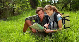 Hiker couple with map pointing ahead stock video