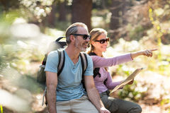 Hiker couple with map pointing in the distance Royalty Free Stock Image