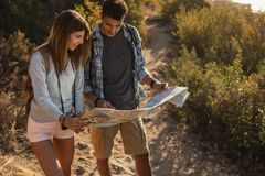 Hiker couple with navigation map on mountain trail. Young man and woman using map to find the direction to the destination royalty free stock photography