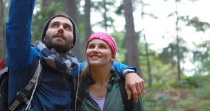 Hiker couple pointing at distance. In forest, 4k stock video