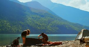 Hiker couple preparing tent near riverside 4k stock footage