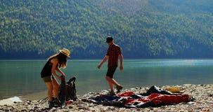Hiker couple preparing tent near riverside 4k stock video footage