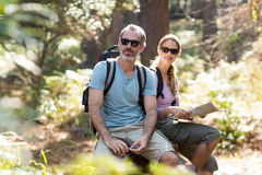 Hiker couple sitting on rock with map Royalty Free Stock Images